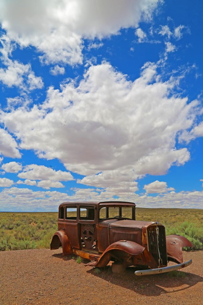 Seven Things to Do in Petrified Forest National Park located in Arizona, Travel the park road to see sites including Historic Route 66, Desert Views, Blue Bentonite Mesas, petrified wood, petrified logs, petroglyphs and the Painted Desert Inn which is a National Historic Landmark
